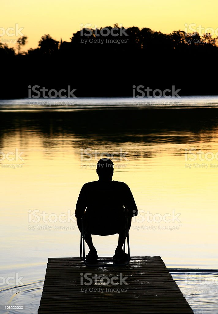 Silhouette of Man Sitting on Dock at Sunset royalty-free stock photo