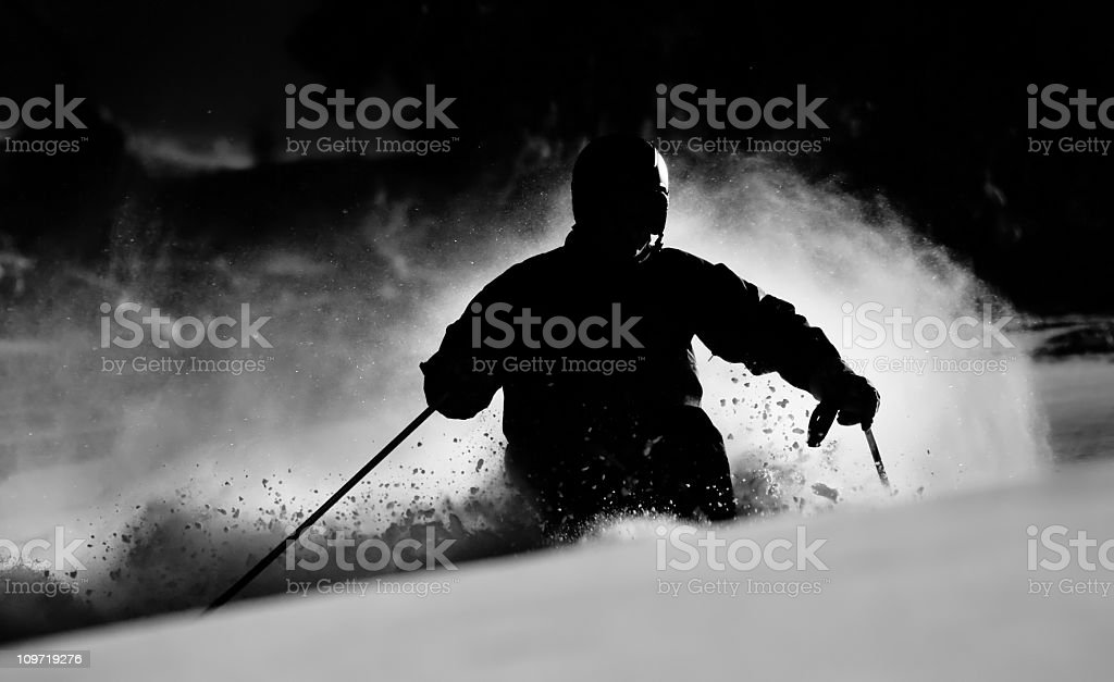 Silhouette of Man Skiing and Carving in Snow stock photo