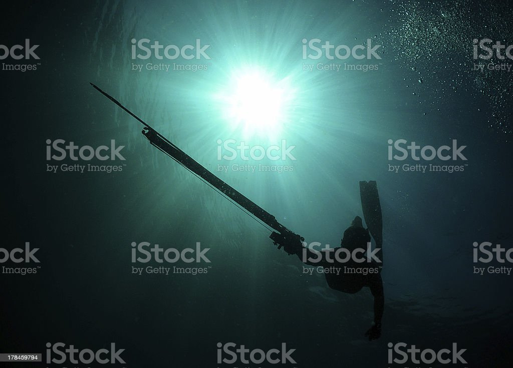Silhouette of man spearfishing stock photo