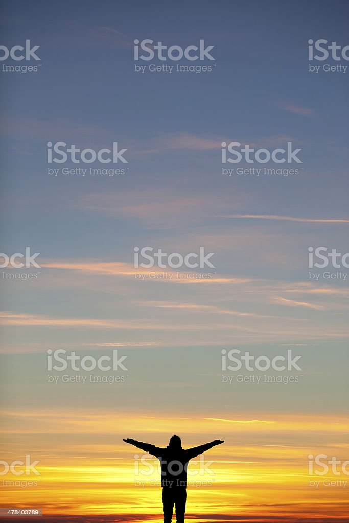 silhouette of man spreading arms in sunset sky stock photo