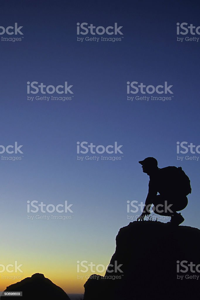 silhouette of man squatting at sunset sky landscape edge royalty-free stock photo