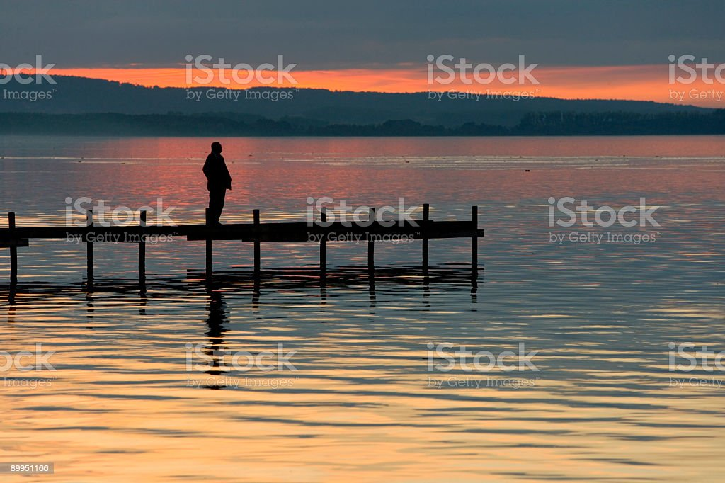 Silhouette of Man Standing On Lakeside Jetty at Dusk (XXL) royalty-free stock photo