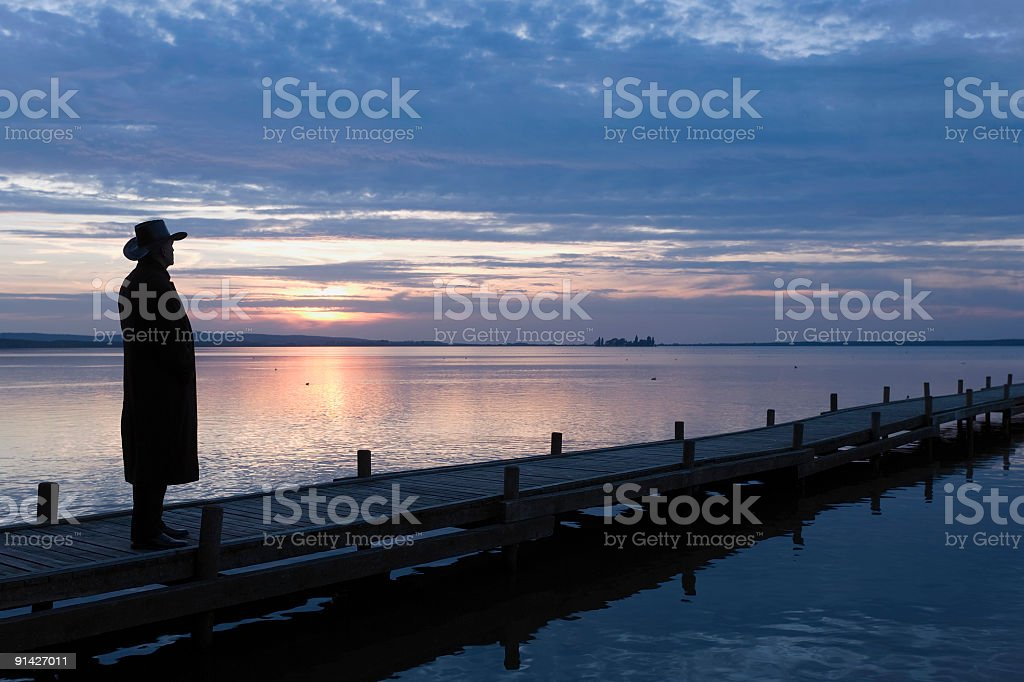 Silhouette of man standing on lakeside jetty at sunset (XXL) royalty-free stock photo