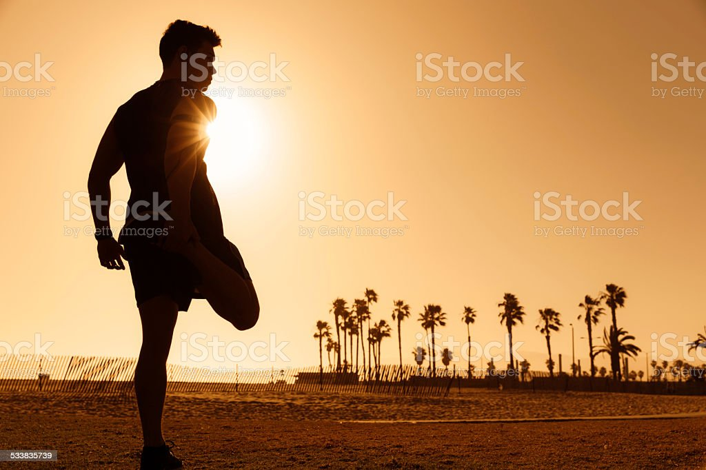 Silhouette of Man Stretching at Venice Beach stock photo