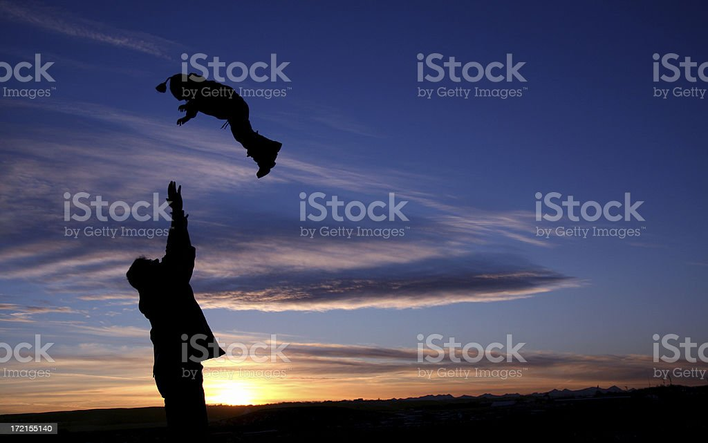 Silhouette of Man Throwing Child in the Air royalty-free stock photo