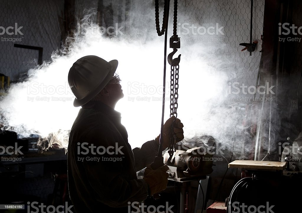 Silhouette of man using chain hoist in workshop. royalty-free stock photo