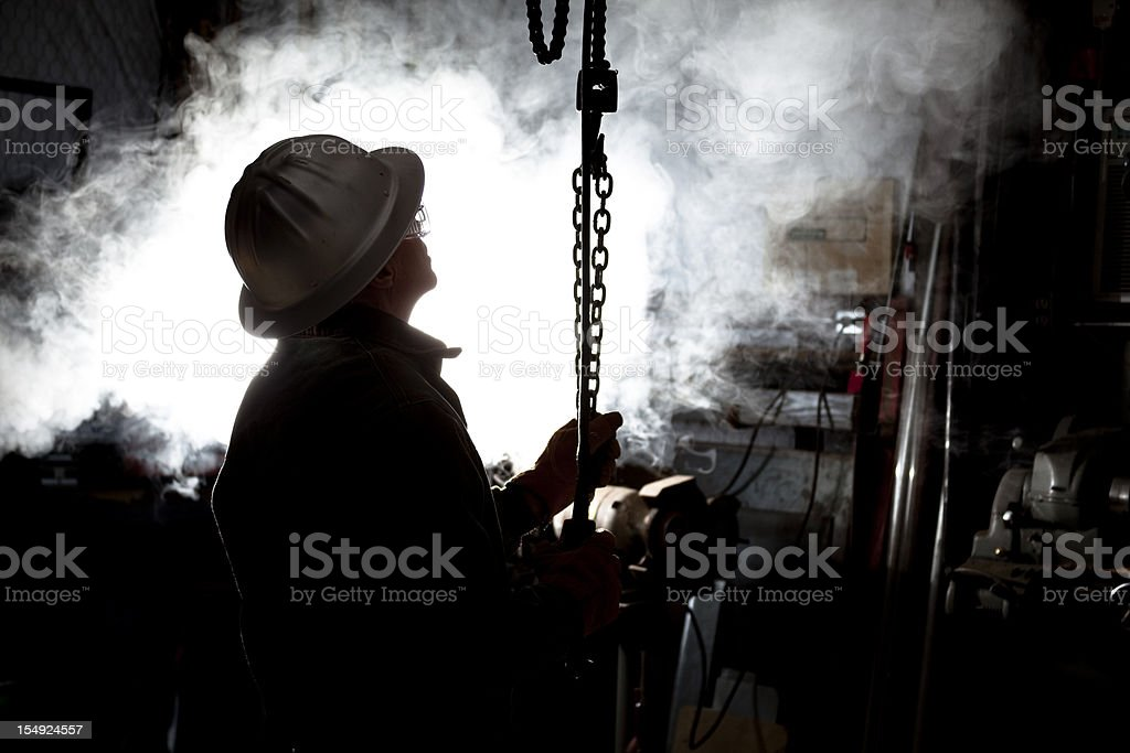 Silhouette of man using chain hoist in workshop. stock photo