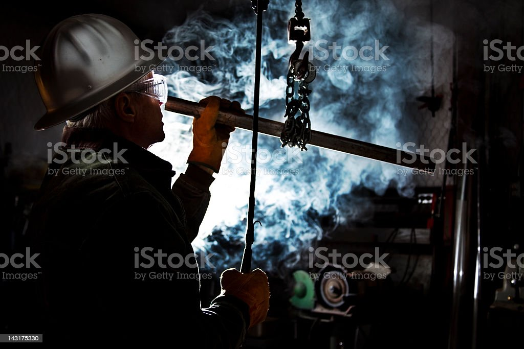 Silhouette of man using chain hoist in workshop.  Steam background royalty-free stock photo