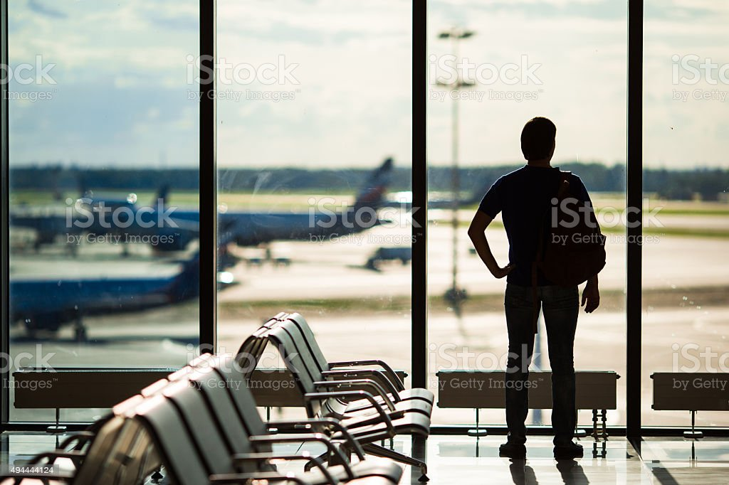Silhouette of man waiting to board a flight in airport stock photo