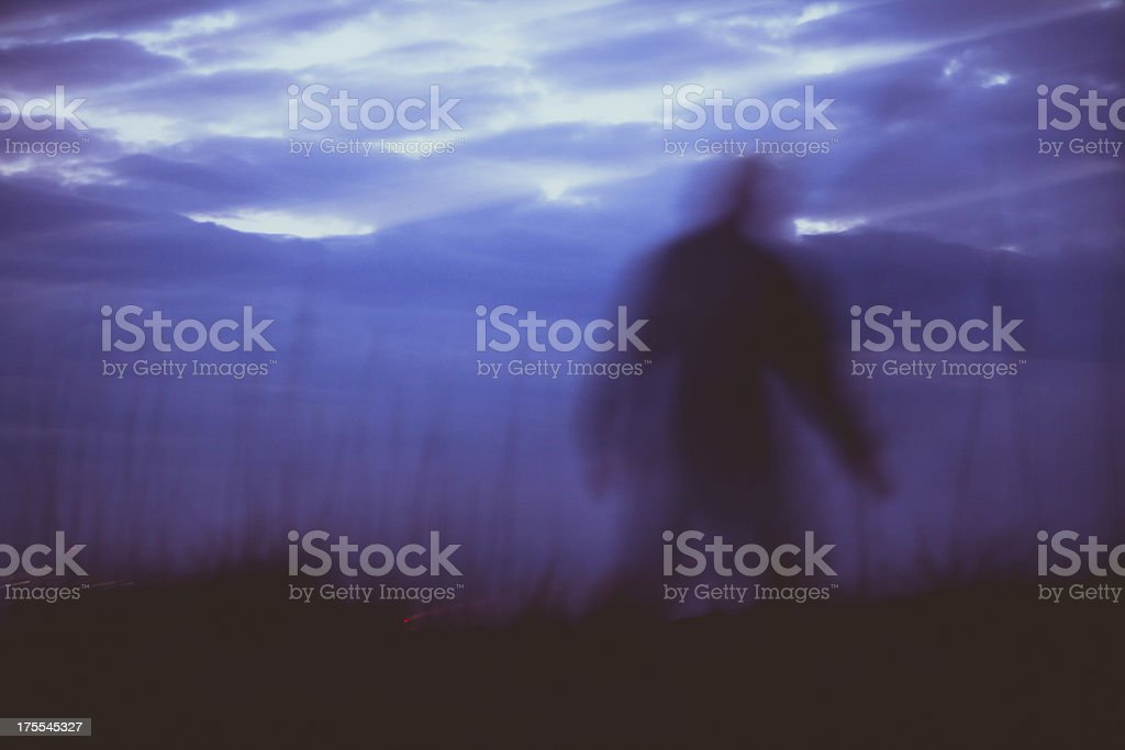 Silhouette of man walking along coastline at sunset royalty-free stock photo