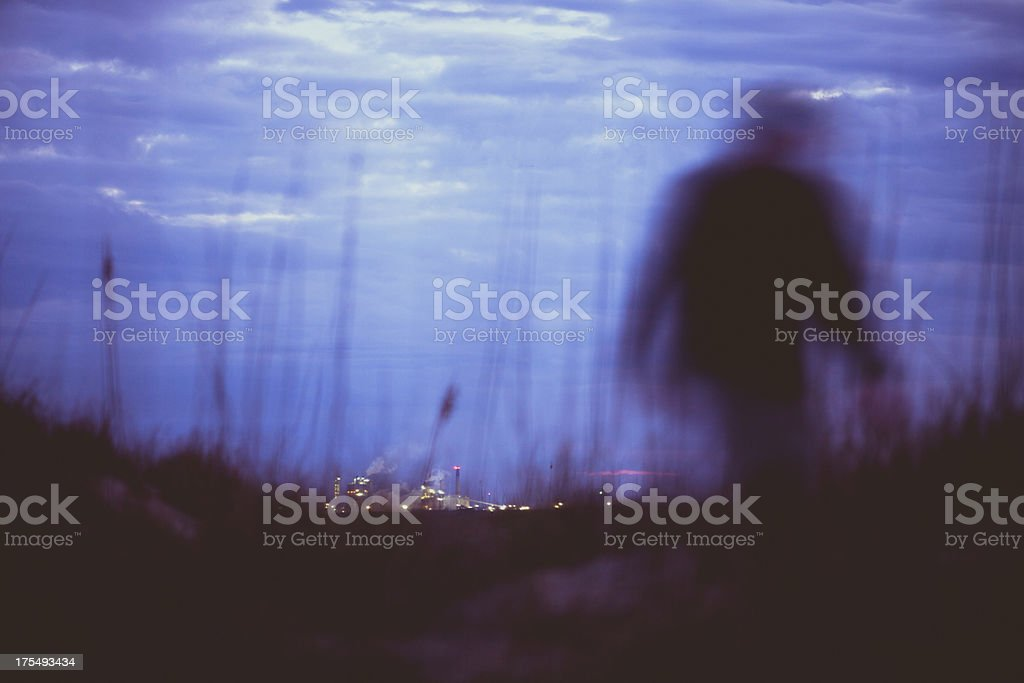 Silhouette of man walking along coastline with skyline in distance royalty-free stock photo