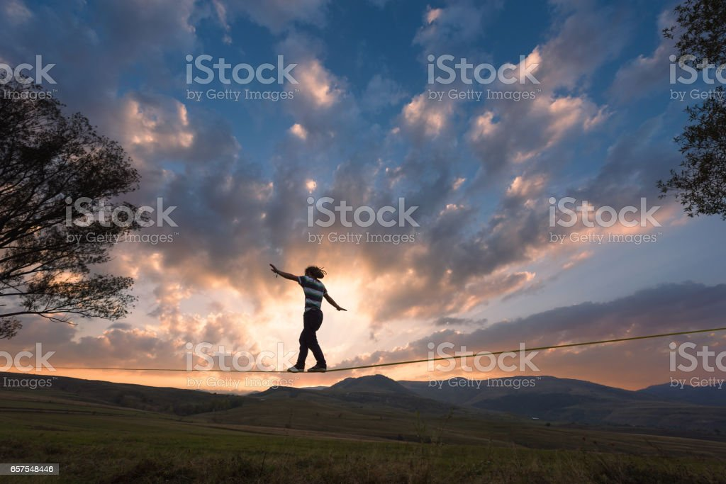 Silhouette of man walking on slackline tight rope in the dusk stock photo