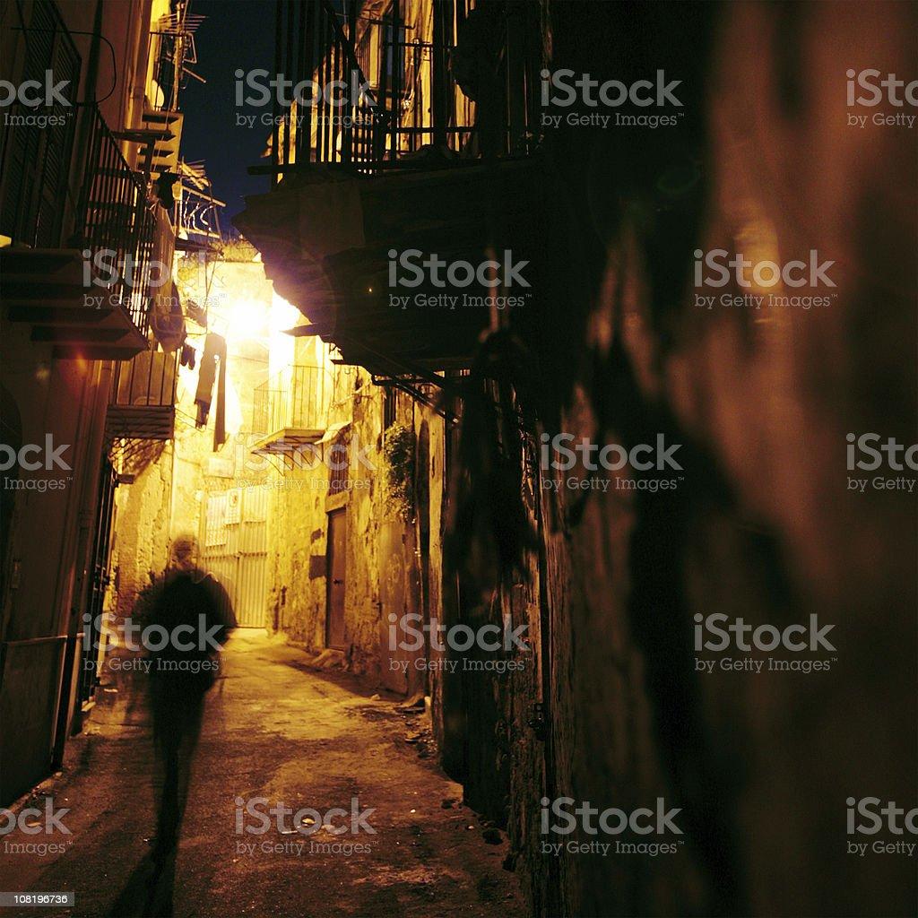 Silhouette of Man Walking Through Narrow Street royalty-free stock photo