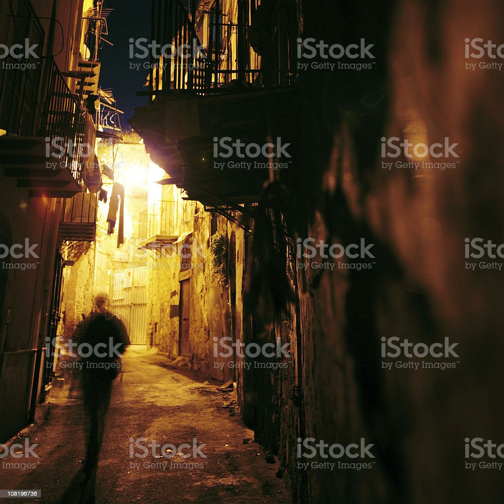 Silhouette of Man Walking Through Narrow Street stock photo