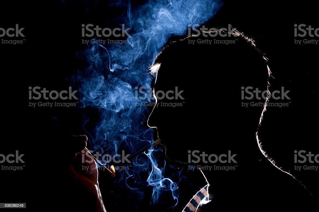 Silhouette of man who lights the cigarette in the dark stock photo