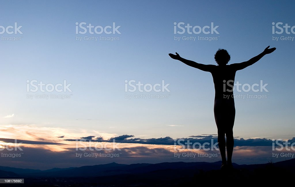 Silhouette of Man with Arms Outstretched Towards Sky at Sunset stock photo