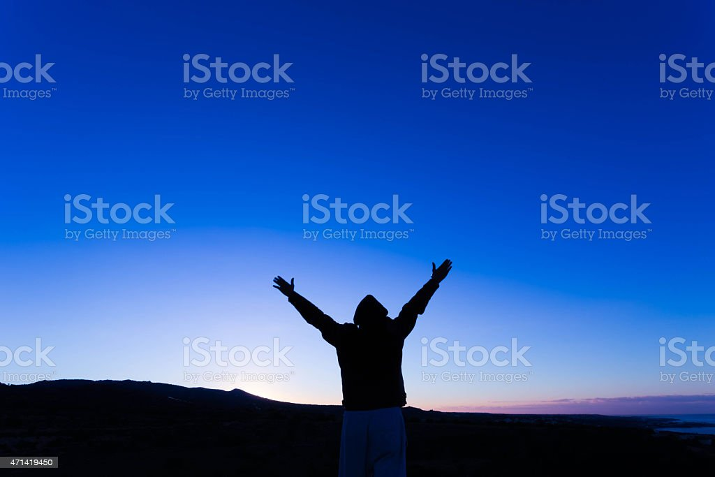 Silhouette of man with arms up, at Dawn stock photo