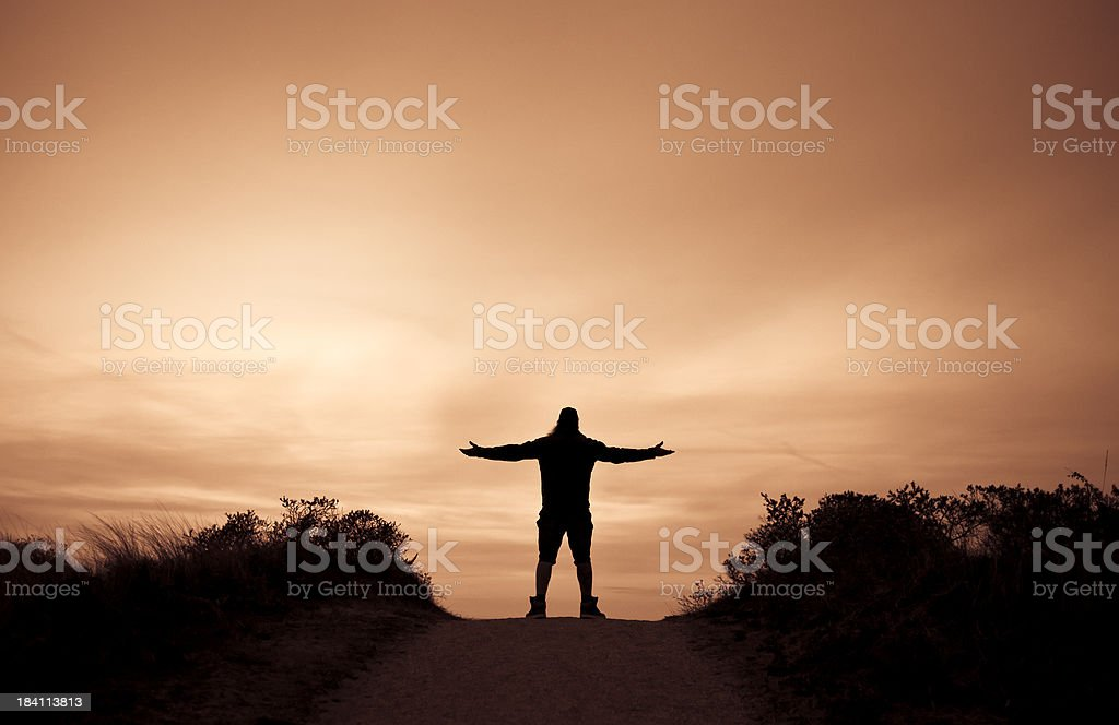 Silhouette Of Man With Outstretched Arms In A Path, Sunset royalty-free stock photo