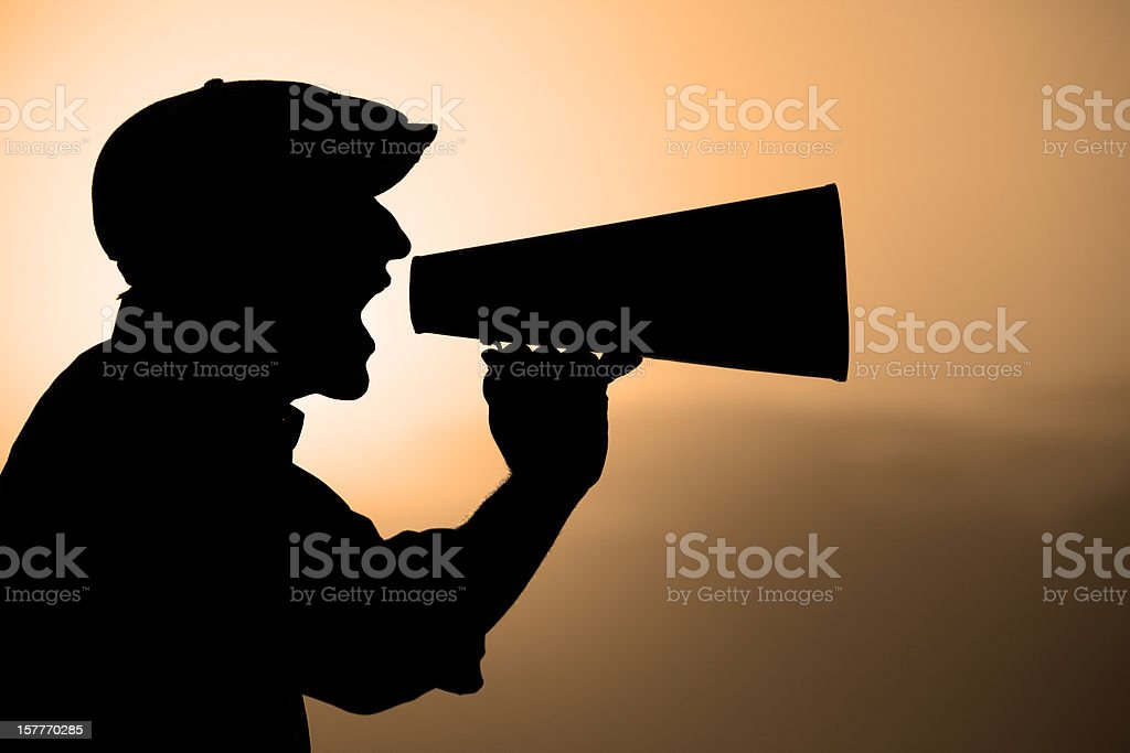 Silhouette Of Man Yelling Trough A Megaphone In Sunset stock photo