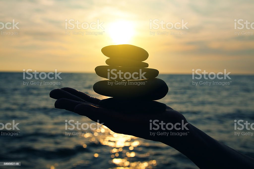 Silhouette OF Man's Hand Holding Stones stock photo