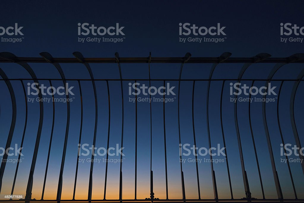 Silhouette of metal fences against a blue and orange sky stock photo