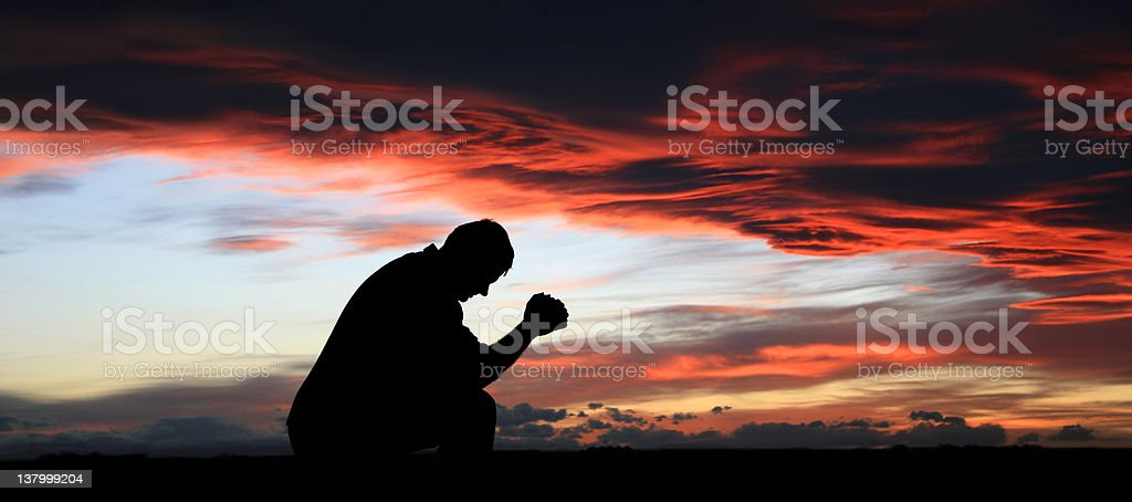 Silhouette of Middle-Aged Man Praying stock photo