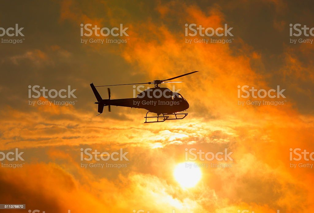 Silhouette of military helicopter at sunset stock photo