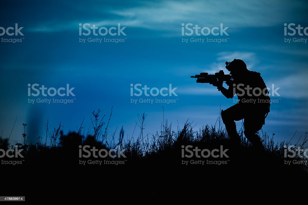 Silhouette of military soldier or officer with weapons at night. stock photo