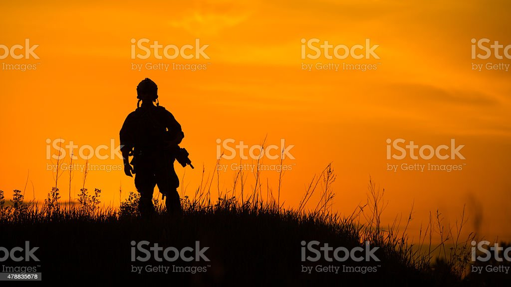Silhouette of military soldier or officer with weapons at sunset stock photo