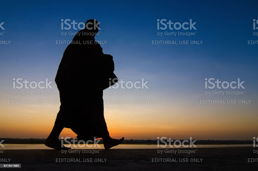 Nakhon Phanom, Thailand - February, 06, 2017 : Silhouette of monk feet walking on concrete ground for people offering food in twilight morning near Mekong river bank at Nakhon Phanom, Thailand stock photo