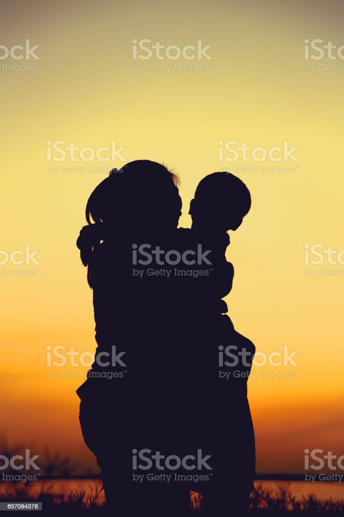 Silhouette of mother and child enjoying at riverside. stock photo
