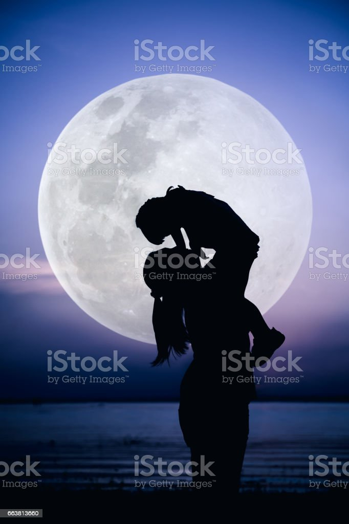 Silhouette of mother and child enjoying the view at riverside. stock photo