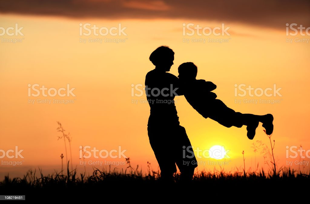 Silhouette of Mother and Child Playing at Sunset stock photo