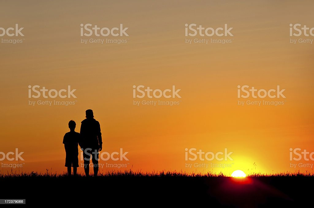 Silhouette of mother and child watching sunset royalty-free stock photo