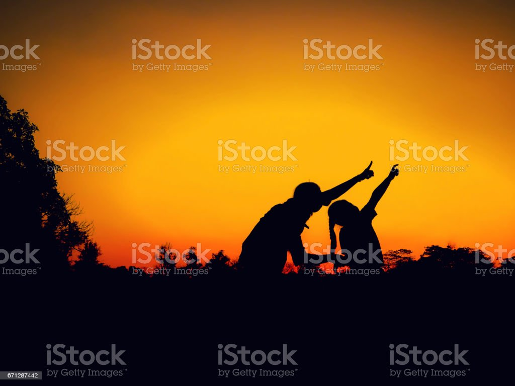 silhouette of mother and little daughter play at sunset stock photo