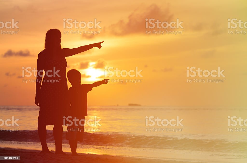 silhouette of mother and son at sunset beach stock photo