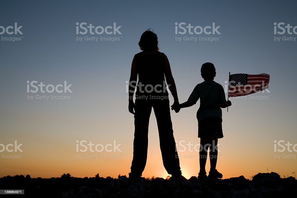 Silhouette of mother and son on horizon during sunset royalty-free stock photo