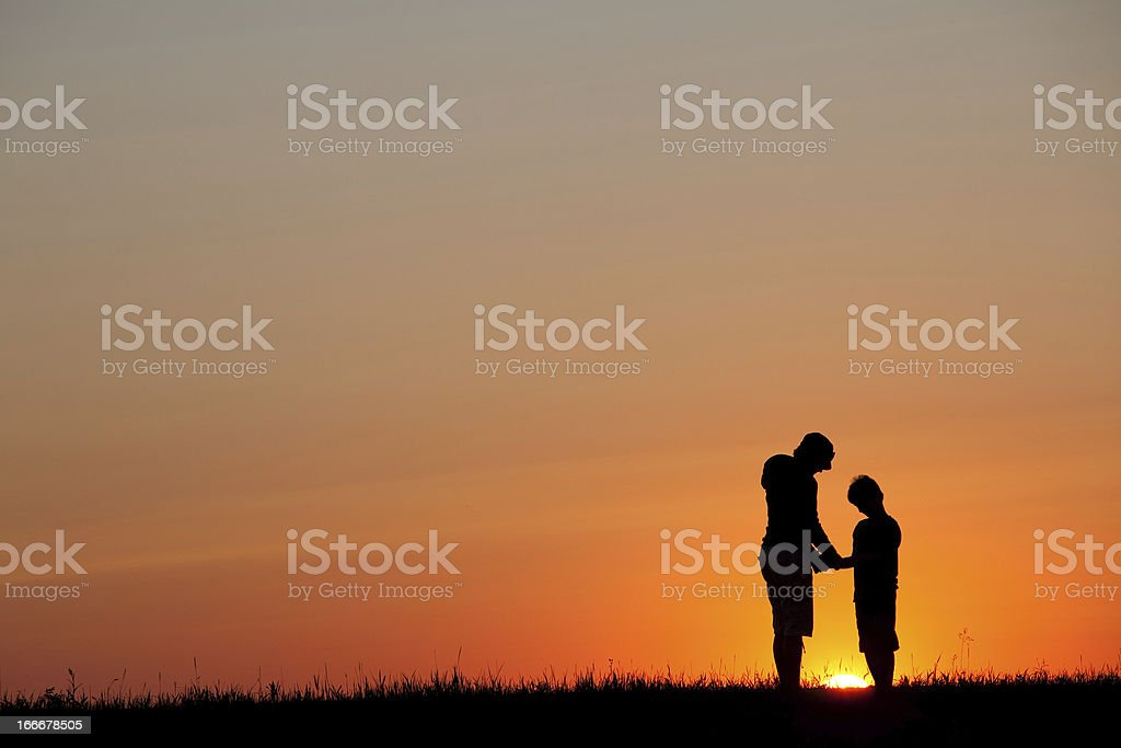 Silhouette of Mother and Son Praying royalty-free stock photo