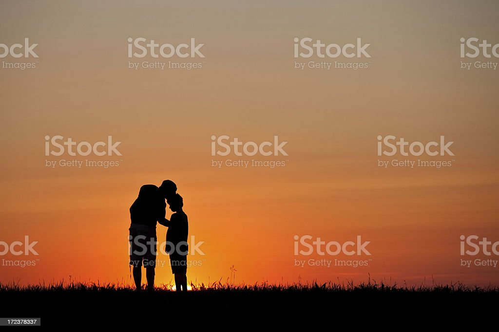 Silhouette of Mother Kissing A Child on Forehead royalty-free stock photo