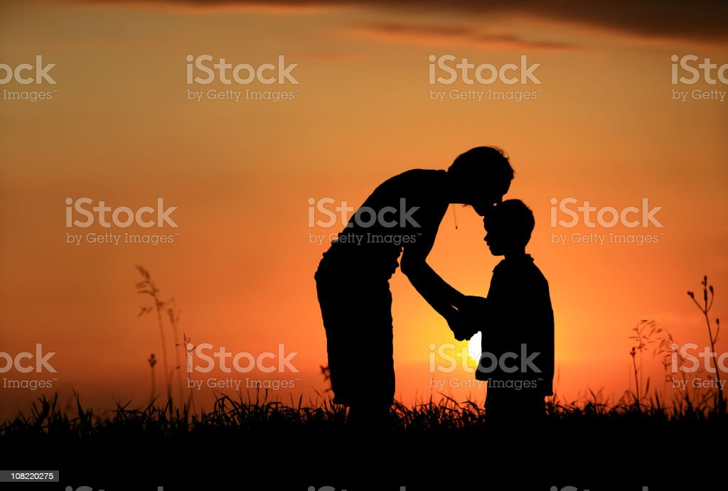 Silhouette of mother kissing child on head royalty-free stock photo