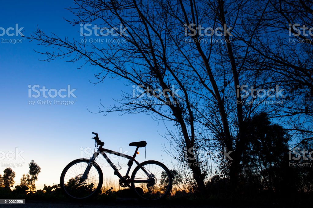Silhouette of Mountain bike at sunset stock photo