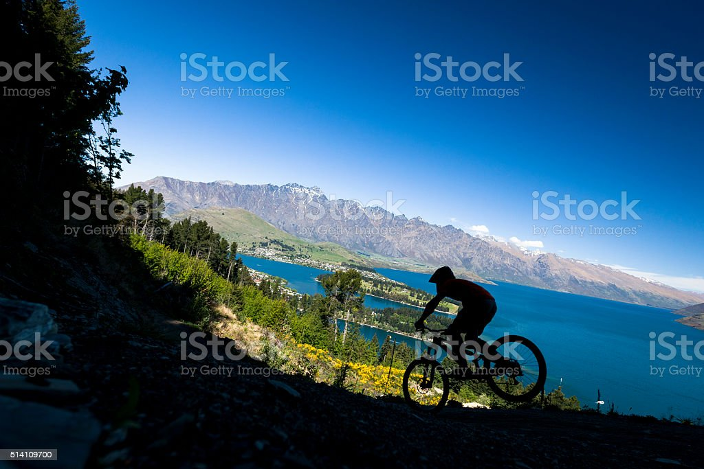 Silhouette of mountain bike rider in Queenstown, New Zealand stock photo
