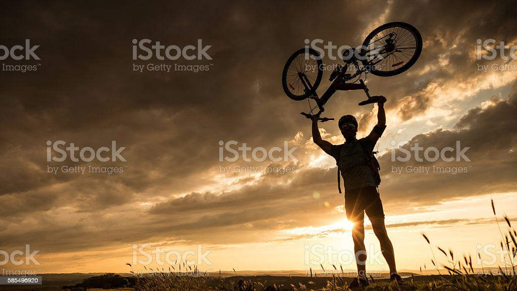 Silhouette of mountainbiker at the top stock photo