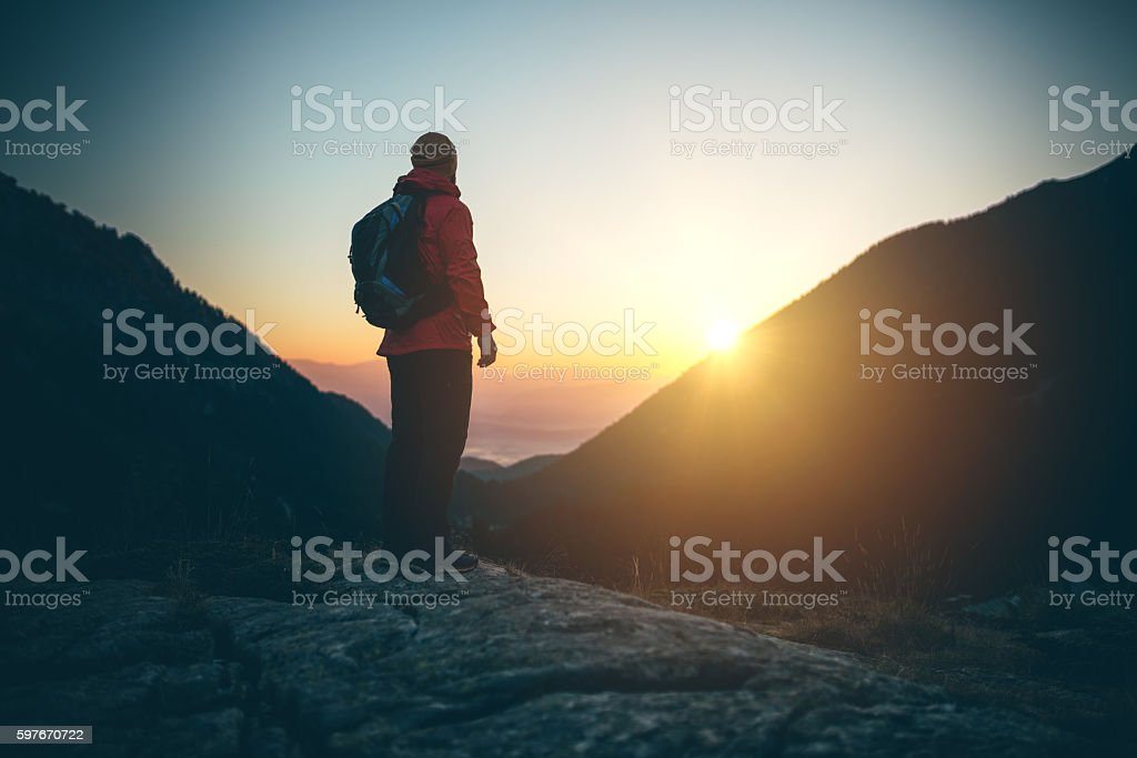 Silhouette of mountaineer on top of the mountain stock photo