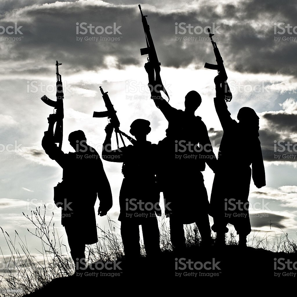 Silhouette of Muslim militants with rifles stock photo