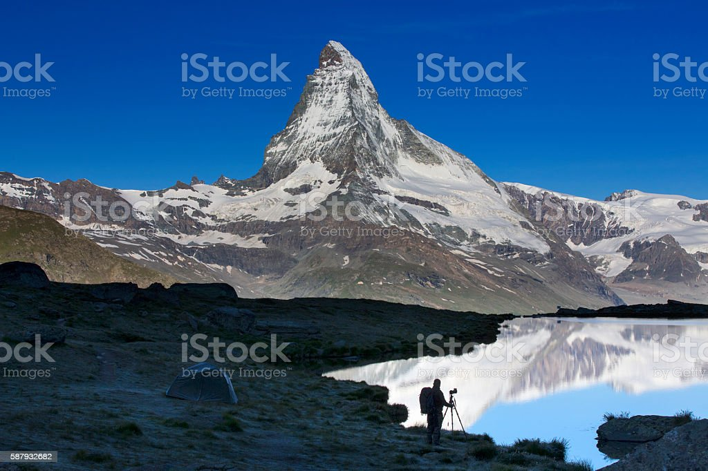 Silhouette of Nature photographer at Matterhorn with Stellisee in foreground stock photo