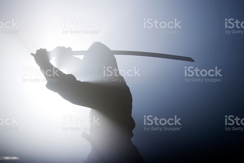 Silhouette of ninja swinging sword in fog stock photo