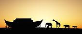 Silhouette of Noah's Ark with animals at sunset