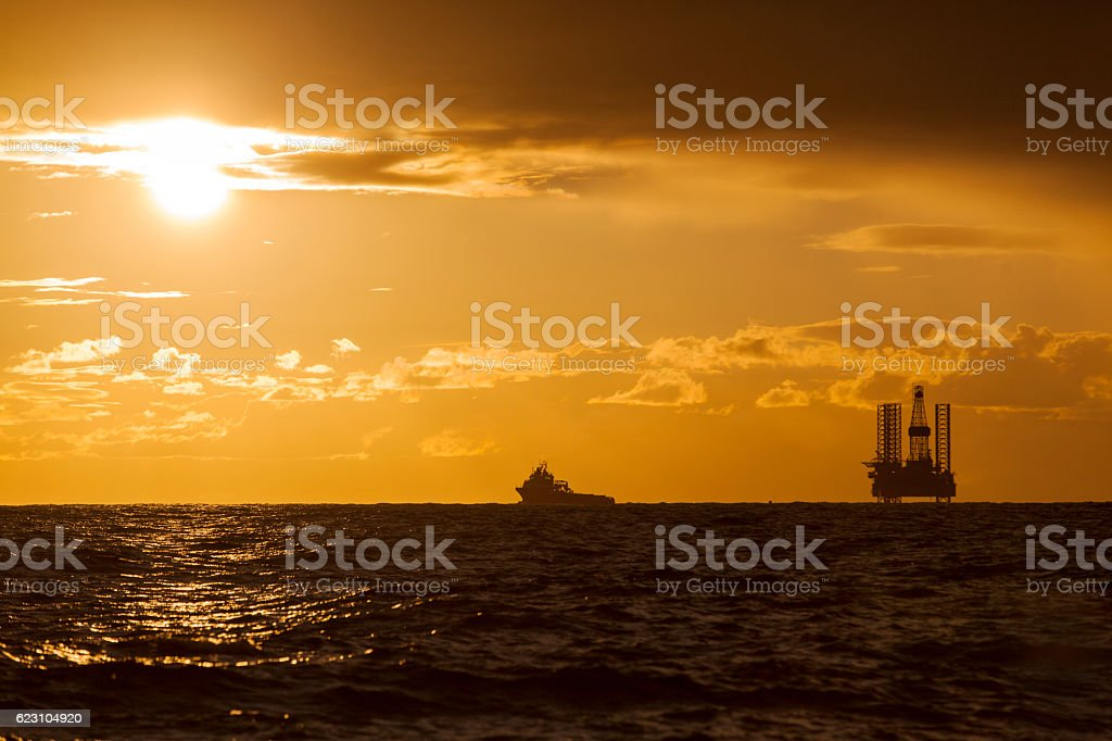 Silhouette of Offshore Jack Up Rig and tug ship stock photo