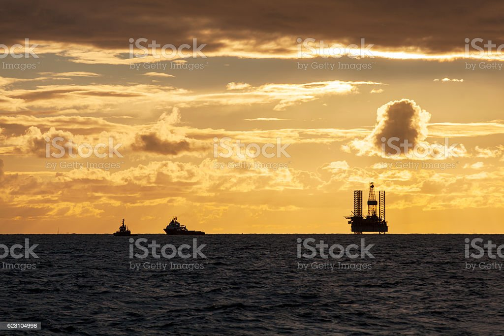 Silhouette of Offshore Jack Up Rig and tugs stock photo